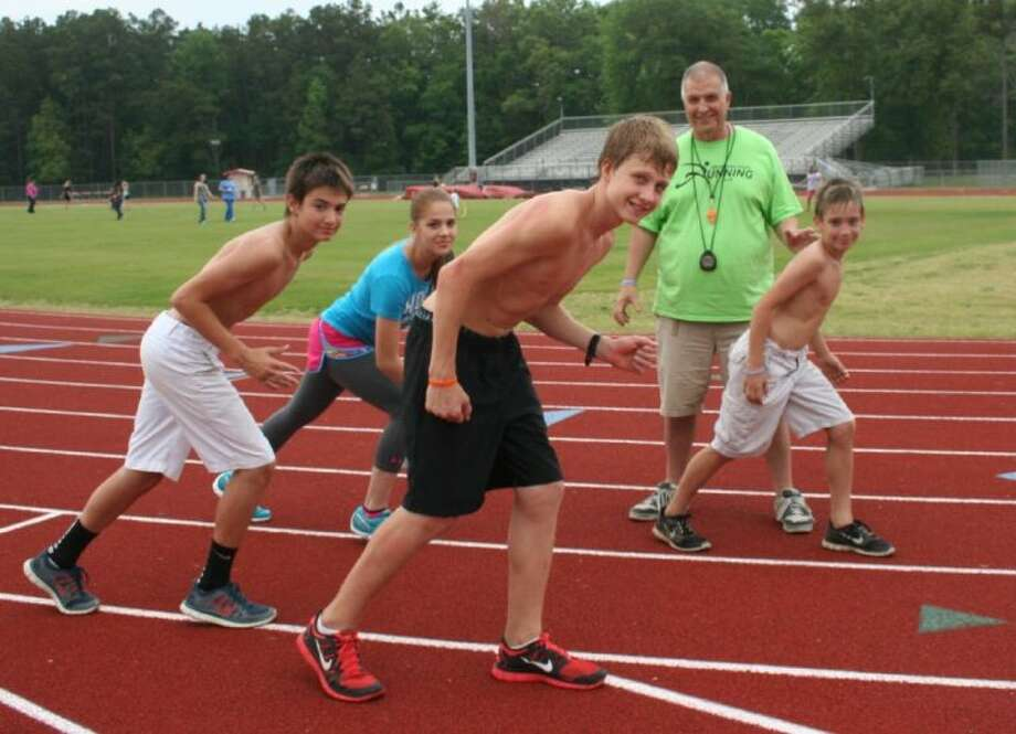 Kaleb Nelson, Kellie Parker, Jacob Garrison and Jakob Nelson all participated in the Fantastic Family Fitness Night on April 24. Coach Bill Horewitch, the organizer of the event, also helps coach the students that are all part of the Splendora Youth Running Club. Photo: STEPHANIE BUCKNER
