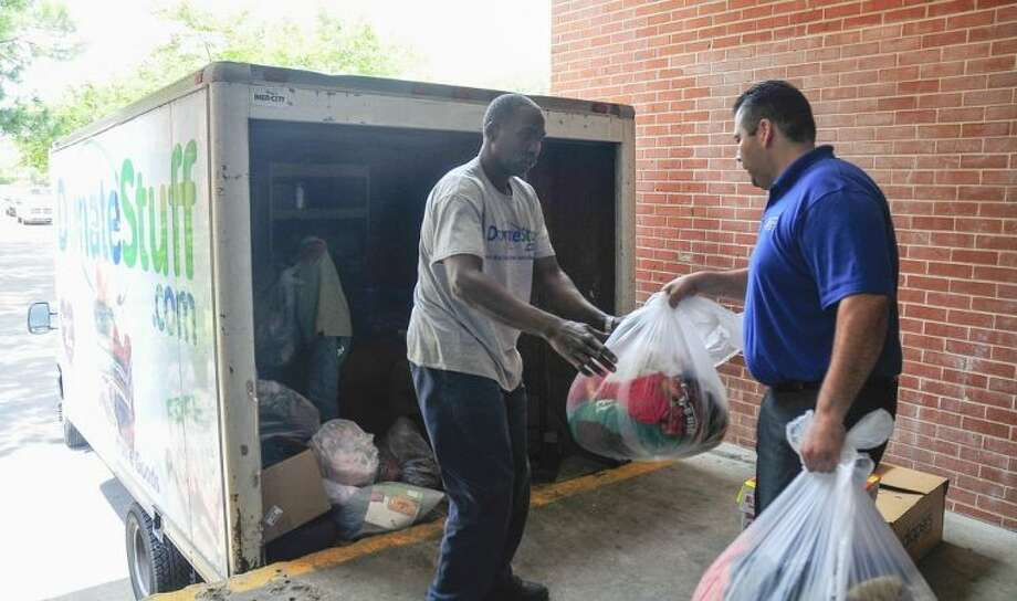 Pictured, (left to right) Purple Heart representative, Joseph Pulling, collects donated clothing from Saul Zarco, educational planner with San Jacinto College. Photo credit: Jeannie Peng-Armao, San Jacinto College marketing, public relations, and government affairs department.