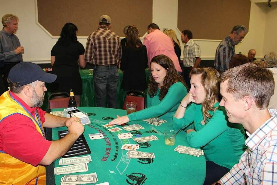 Lion Trent Perez deals poker to Pearland Police Sgt. Derek Dunham, his wife and a friend.