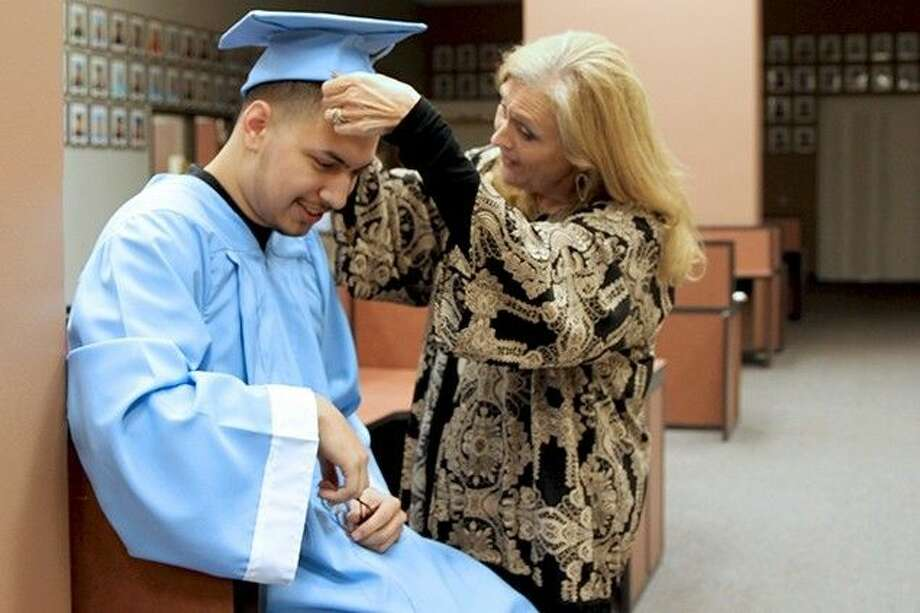 Community School graduate Mark Cruz gets help putting on his cap and gown by one of his favorite teachers, Donna Groce.