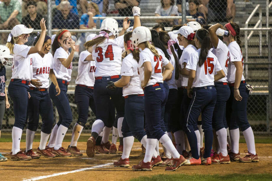 The Lady Eagles celebrate as Shelby McGlaun (34) crosses home plate after hitting an home run over the fence during Atascocita's matchup against College Park on April 25, 2014, at Atascocita High School.