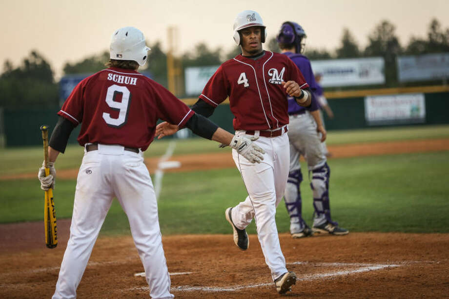 Magnolia's Noah McGowan (4) slaps hands with Mason Schuh (9) after both players were batted into home during the high school baseball game against Montgomery on Friday, April 25, 2014, at Magnolia High School. Photo: Michael Minasi