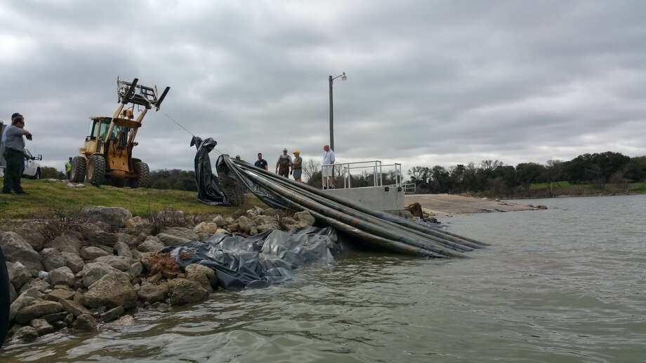 Crews removed tarps covering the bottom of the boat ramp area at Lake Waco where zebra mussels were discovered only to find that a few zebra mussels had survived. The tarps were 35 feet wide by 150 feet long and weighed about a half ton each. Photo: Texas Parks And Wildlife Department