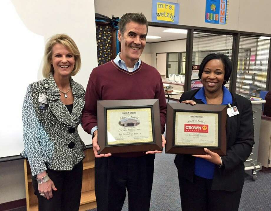 From left, Leslie Francis, director of marketing and business relations; Greg Donovan, general manager of Crown Relocations; and Tonya Goree, Lee Elementary School principal; display certificates of adoption after formalizing their Adopt-a-School partnership on April 6