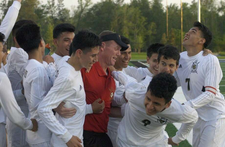 Porter head coach John Brown celebrates with his team following a 4-2 victory against Fort Bend Bush on Thursday, April 2, 2015, at Texan Drive Stadium.