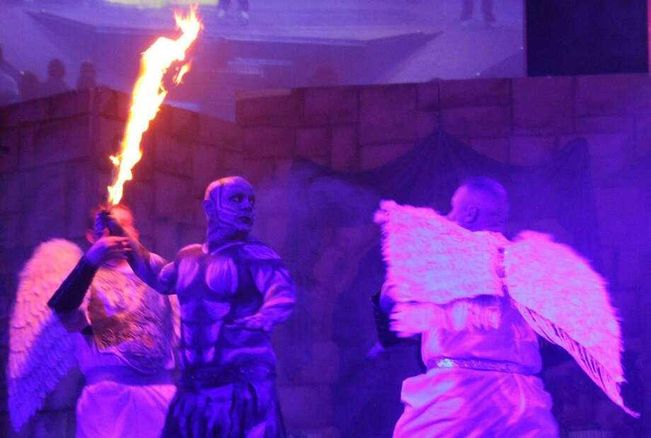 Lucifer (David Warren) wields a fiery brand as he is approached by two angels preparing to cast him out from Heaven. Photo: Jacob McAdams