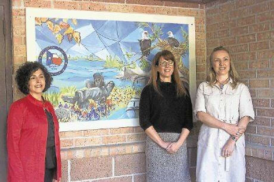 """WWAF 2014 Community Art Collaborators Jenny Wright, WWAF Director, Allison Hulett, MOW Exec Director and Carolina Dalmas, Artist with Woodlands Art League show off a mural, part of """"Woodlands Alive,"""" a two-panel art mural installed at The Woodlands Friendship Center's Meals on Wheels location."""