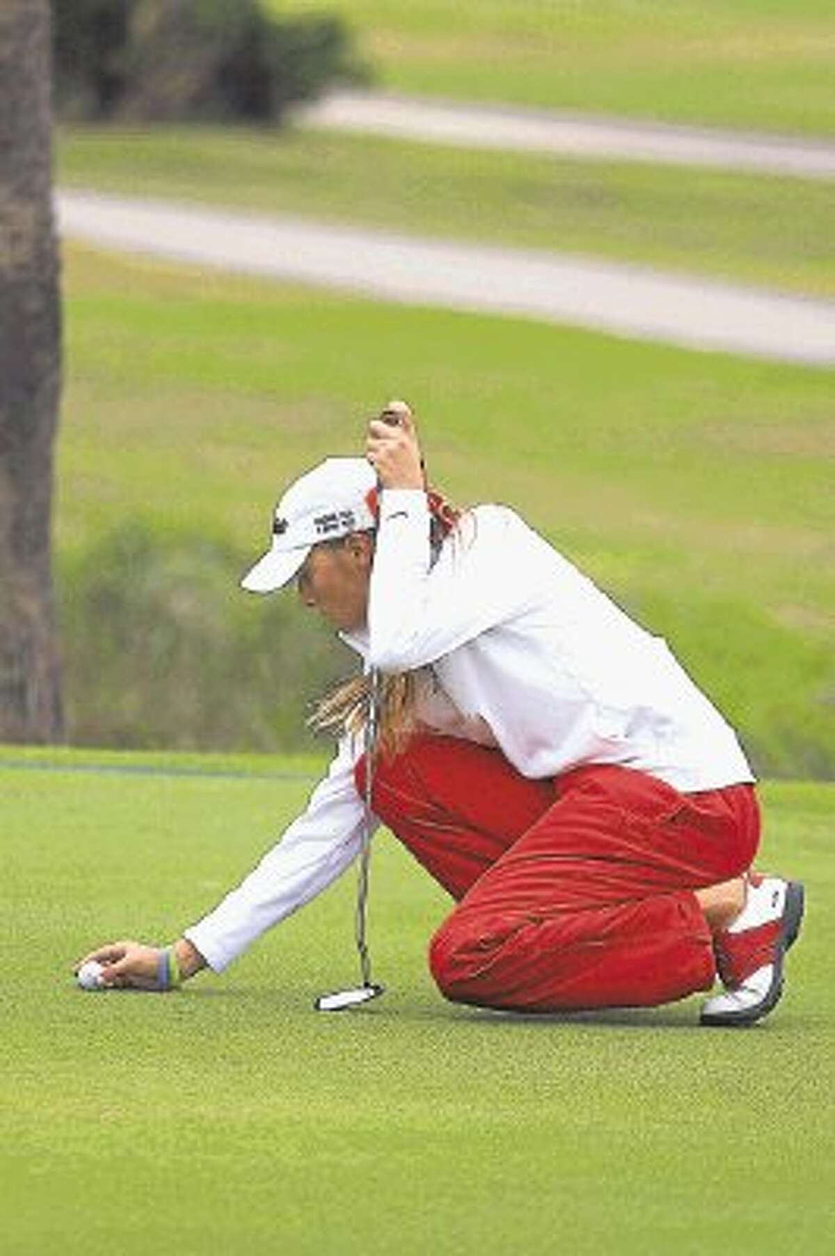 Clear Lake golfer Kari Bush marks her ball during the Region III-5A golf tournament. Bush shot 73-72--145 to finish in second place, just a stroke behind winner Maddie Luitwieler of Cinco Ranch.