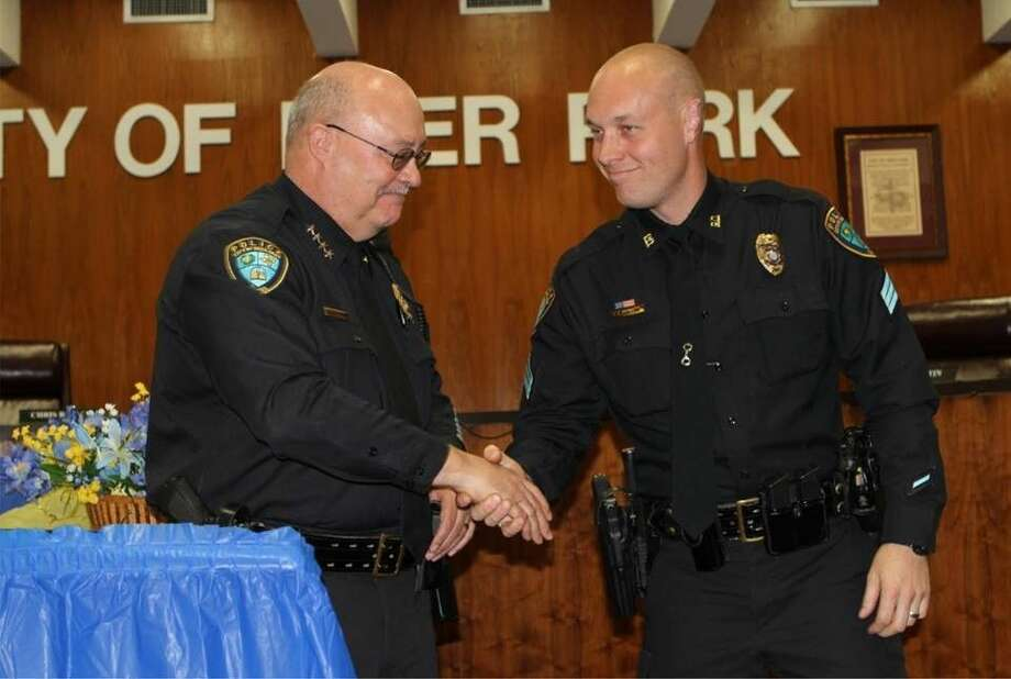 Sergeant Bryan Miller receives a badge and a handshake from Chief Greg Grigg.