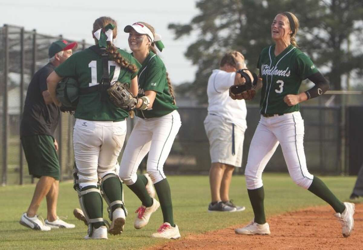 The Woodlands third baseman Kaitlyn Stavinoha, second from left, celebrates a successful pickoff attempt with teammates as Klein Collins coach Rosemary Rhodes, background, reacts during Game 2 of a bi-district playoff series on Saturday at Klein Oak High School. To view or purchase this photo and others like it, visit HCNpics.com.