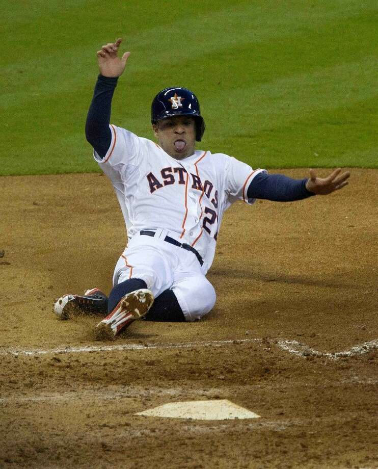 The Astros' Jose Altuve slides into home plate in their 2-0 victory over the Indians on Monday.