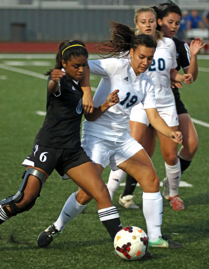Evangeline Isis (19) and Jordan Loya (20) of Clements work together to steal the ball from Clear Springs, April 7 in Pearland. Photo: Kar B Hlava