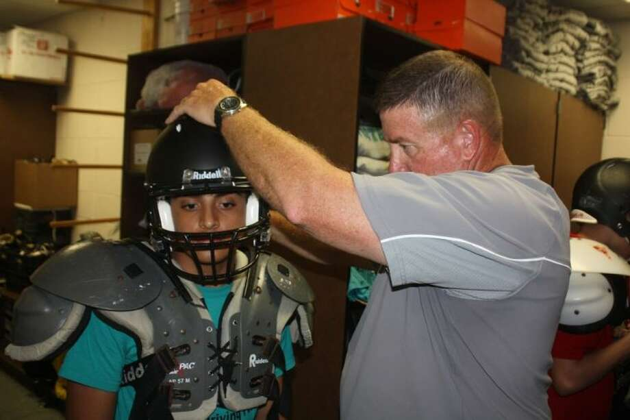 Memorial High head football coach Chris Quillian checks the helmet of a potential varsity player Friday afternoon as the coaching staff prepared for the start Monday afternoon of spring drills. Photo: Robert Avery