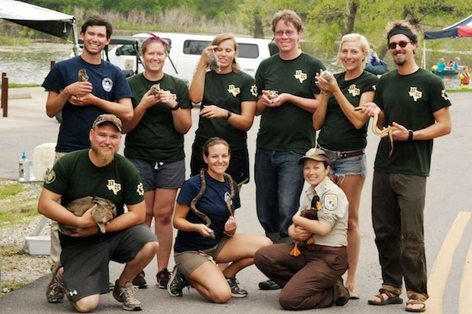 Workers from the Texas Conservation Corps, in green, and interns at the Trinity River National Wildlife Refuge, in blue, pose with some of their friends during the Earth Day celebration at Champion Lake on Saturday, April 26. Pictured are Parker Severson, Stephanie Williams, and Laurie Lomas in front, Brandon Bernhardt, Heather McCullough, Caity Veraar, Nick Johns, Erica Keller and Austin Buckingham in back. Photo: CASEY STINNETT / Houston Community Newspapers, 2014