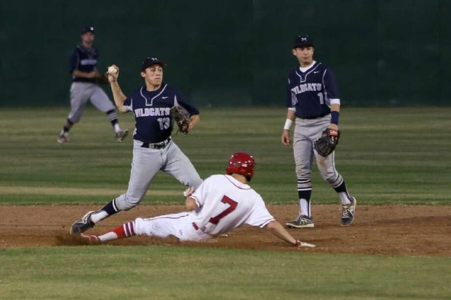 Tomball Memorial's Kyle Larsen (13) throws the ball to first base to complete a double play during the high school baseball game against Tomball on Tuesday, April 22, 2014, at Tomball High School. To view or purchase this photo and others like it, go to HCNPics.com. Photo: Michael Minasi