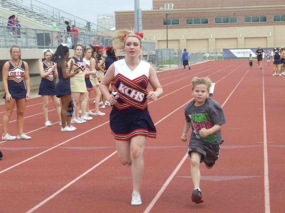 Klein Collins High School freshmen Brooke Townsend helps a student run a relay race at the third annual Kleinwell Fitness Fair on Saturday, April 26.