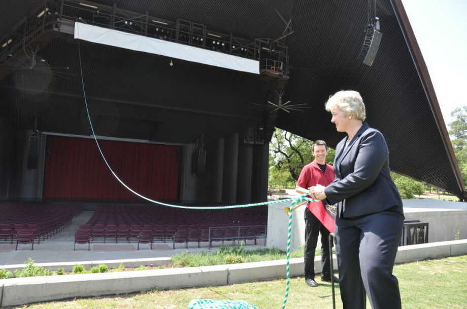 Mayor Annise Parker ceremoniously pulls a rope to unfurl a 50-foot banner, marking the completion of a six-month, $4.7 million roof repair project and the start of the 2014 Miller Outdoor Theatre season, where every seat to every performance is always free to the public. Photo: Photo By David Solce