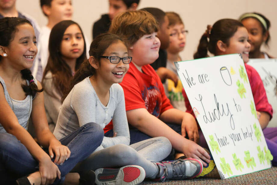 """Students of Horne Elementary sit for photographs with thank you signs to Kenny Thompson, the """"Lunch Angel"""" of Feed the Future Forward, who organized donations to pay oustanding lunch balances at Horne Elementary and several other schools on Monday, Feb. 24, 2014, at Horne Elementary School. (Michael Minasi / HCN)"""