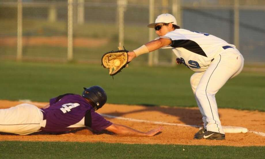 Morton Ranch's Ryan Burciaga slides back to first against Taylor's Kyle Schuberth during a District 19-5A game April 22 at Taylor High School. The Mustangs take the No. 2 seed into the playoffs, meeting Bellaire for a Region III-5A bi-district series. Visit HCNPics.com for more photos. Photo: Alan Warren