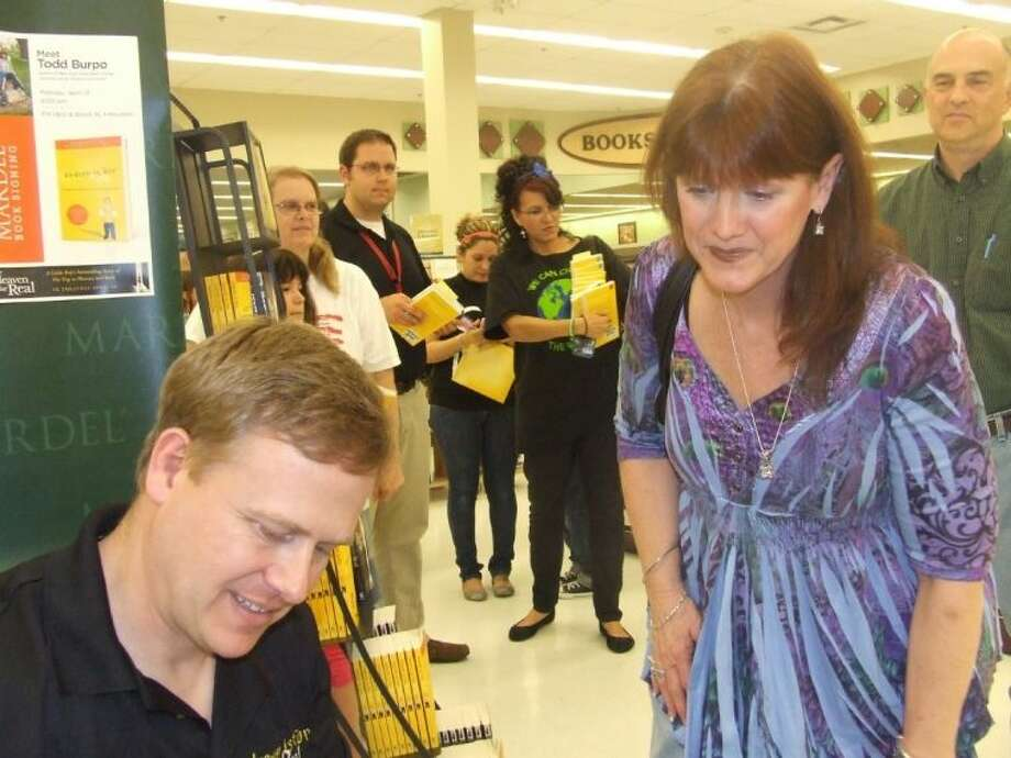 "Todd Burpo, author of ""Heaven Is For Real,"" signs a copy of the book for Tomball resident Leslie Brockley at Mardel Christian Bookstore on Monday, April 16."