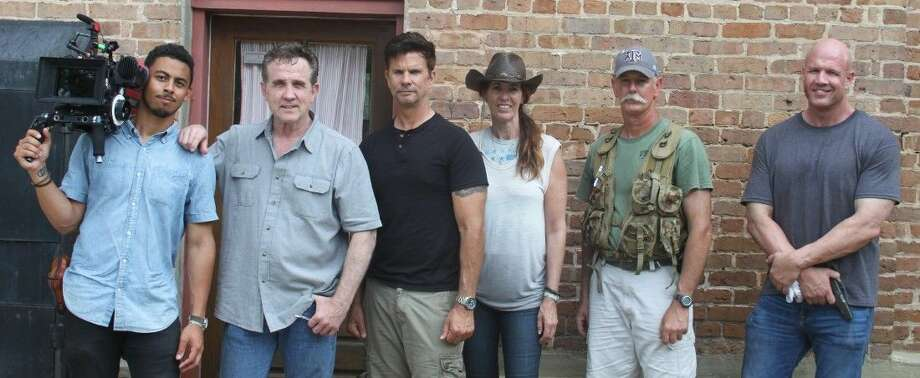 The crew of Walker-Cable productions stand outside of the San Jacinto County Old Jail Museum, which they are using to film one of their scenes. From left to right are Director of Photography D. J. McConduit, Director Chuck Walker, Lorenzo Lamas, Producer Nancy Becker, Prop Master Special Effects Shawn Gorley and Gene Bolton. Photo: Jacob McAdams
