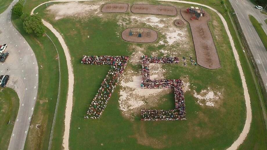 "Lamkin Elementary School students gathered to form the shape of a ""75th"" in recognition of Cypress-Fairbanks ISD's 75th Anniversary school year on April 8 near the school playground. (Photo by Butch Stephens)"