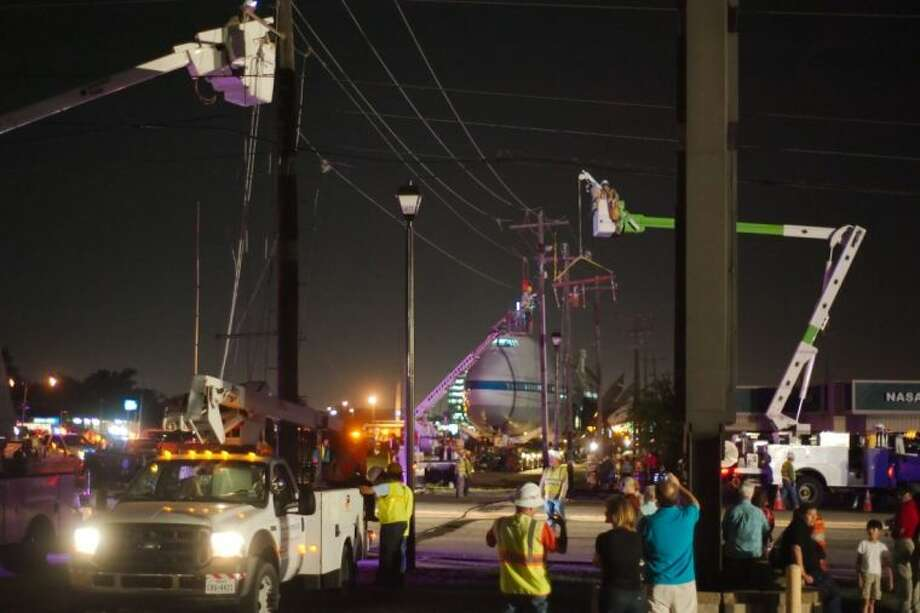 Workers relocate utility wires to make room for the Shuttle Carrier Aircraft as it is moved along NASA Parkway to Space Center Houston Tuesday. Photo: KIRK SIDES