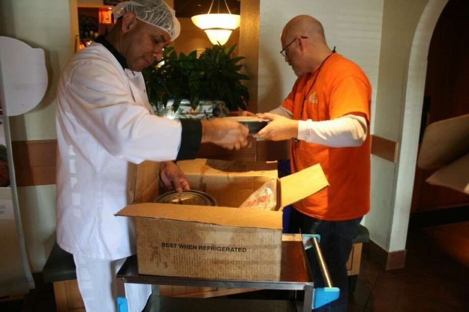 Olive Garden culinary assistant Oscar Nativi helps Mission Greenspoint volunteer Jim Castro pack donated food. Photo: Nate Brown