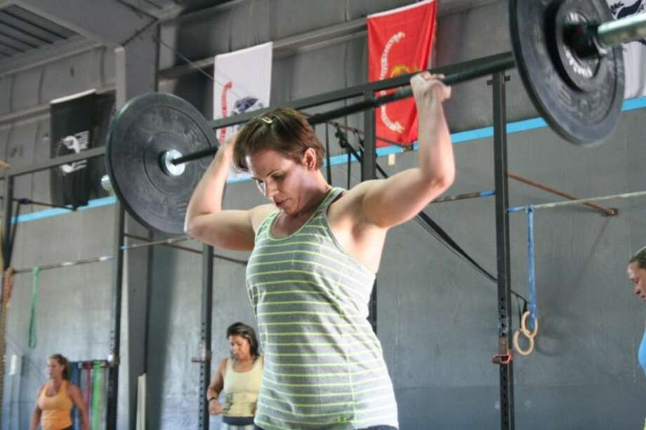 Paula Huggins presses a barbell over her head at Crossfit Thunderdome.