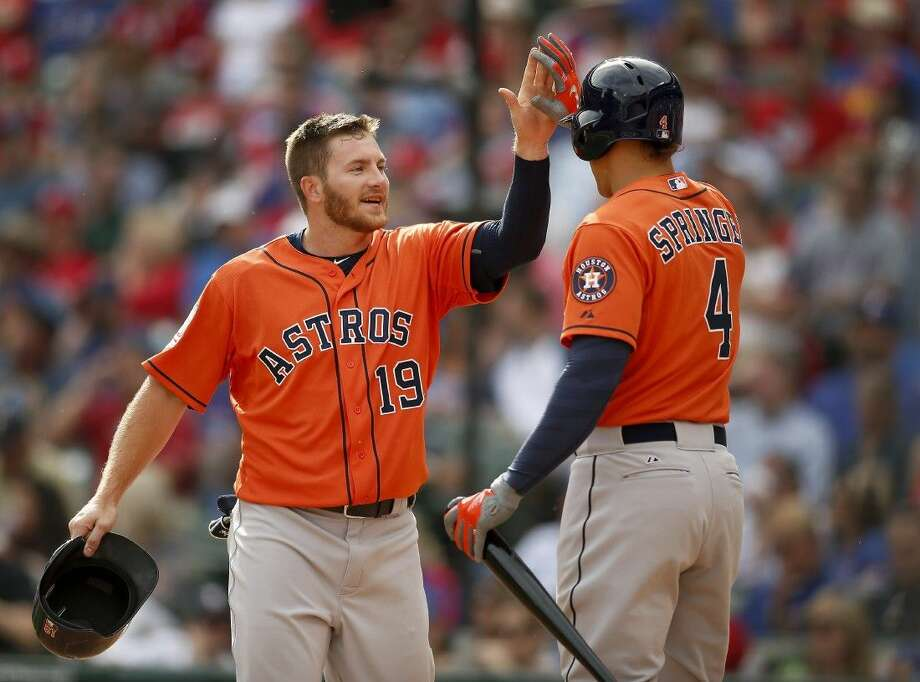 Houston Astros' Robbie Grossman is met at home by teammate George Springer after scoring against the Texas Rangers in the seventh inning in Arlington on Friday.