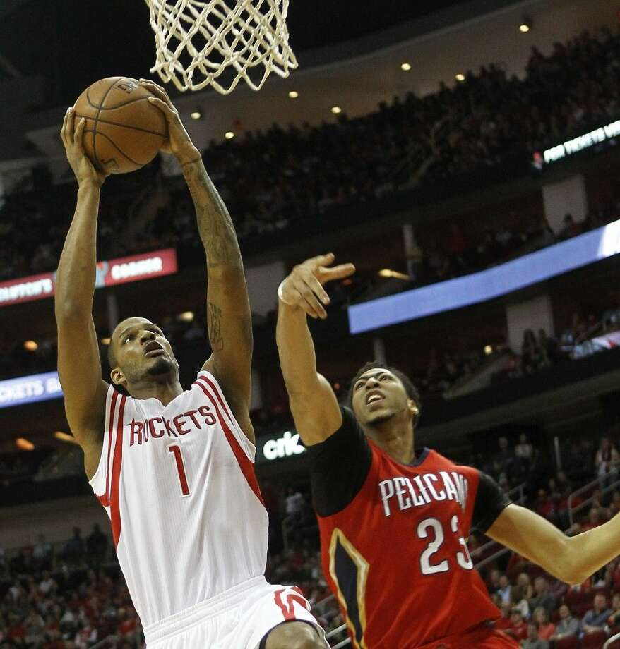 The Rockets' Trevor Ariza, left, drives to the basket as the Pelican's Anthony Davis defends.