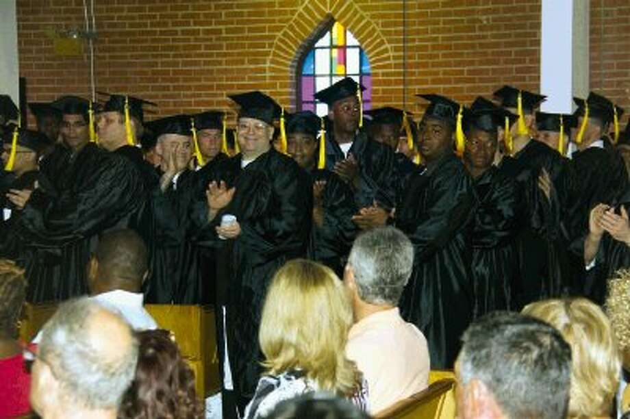 Graduates of the Lee College Huntsville Center rise to thank their family and friends for supporting them Saturday, April 26, at a commencement ceremony held in the Texas Department of Criminal Justice Wynne Unit chapel. Nearly 90 incarcerated offenders earned associate's degrees this year through the Lee College program offered behind bars.