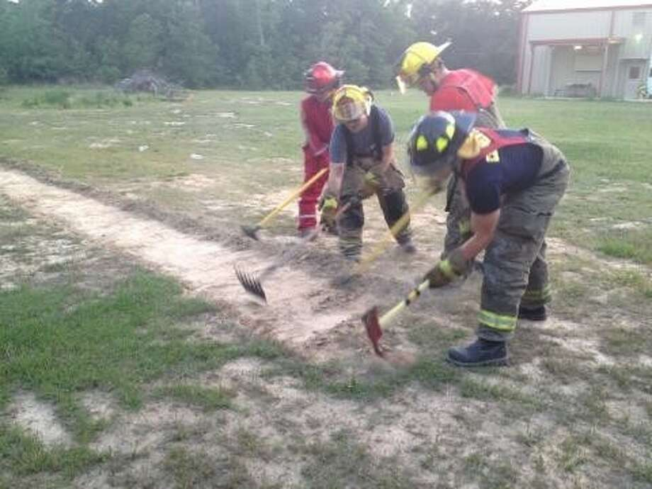 Firefighters from the Huffman Volunteer Fire Department cut a fire break into grass in a wildfire training exercise. Photo: Nate Brown