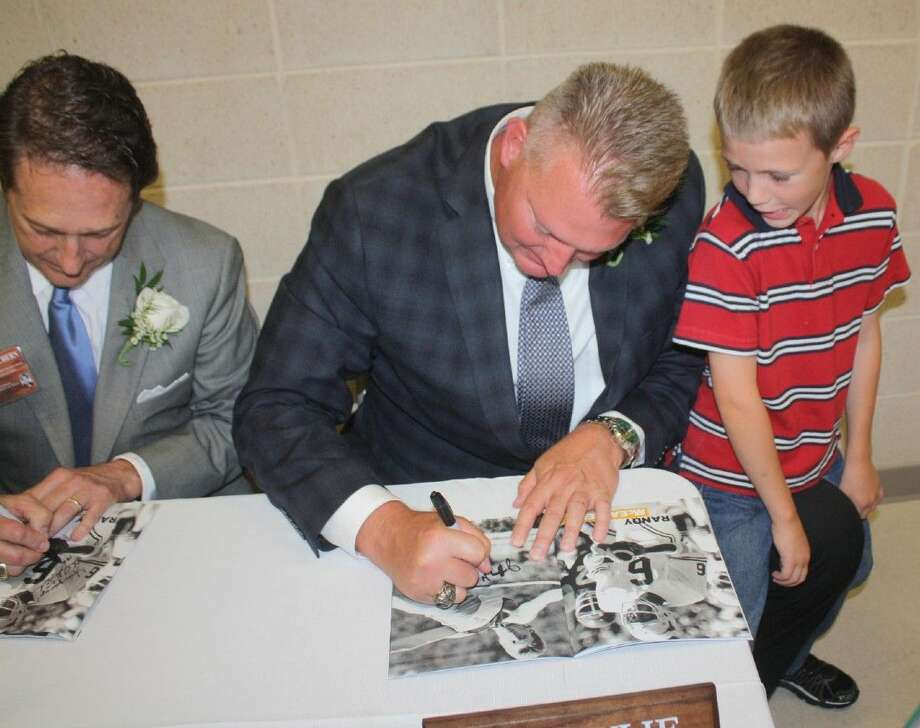 While his 6-year-old son, Ian, looks on, Jeff Wylie autographs a Hall of Fame induction banquet program for a fan after the ceremony. Wylie became the first modern-era male athlete from Pasadena to be inducted Saturday night. Seated next to the famous high jumper from Pasadena is fellow inductee Randy McEachern of Dobie. McEachern guided Dobie to their first district crown, later playing quarterback for the University of Texas, leading the Longhorns to the 1977 SWC crown. Photo: Robert Avery