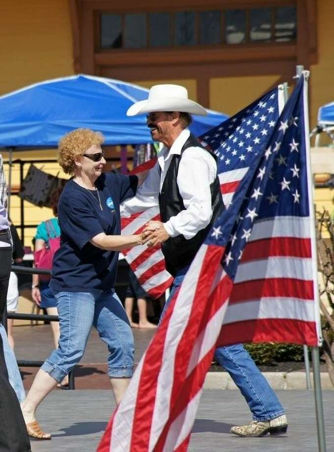Two-steppin' on the dance floor among the flags at the Depot. The Tomball Honky Tonk Music Festival and Two-Step Washers Tournament is set for April 18 at the Depot in Tomball. Photo: Submitted