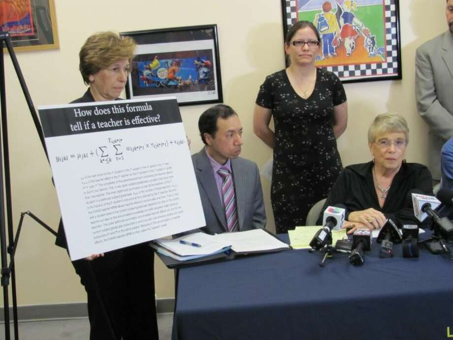 American Federation of Teachers President Randi Weingarten, left, displays the controversial math formula used by Houston ISD that is the subject of a federal lawsuit filed by seven teachers, including Daniel Santos, seated at left, and Myla Van Duyn, standing at right, along with the Houston Federation of Teachers, represented by President Gayle Fallon, seated right.