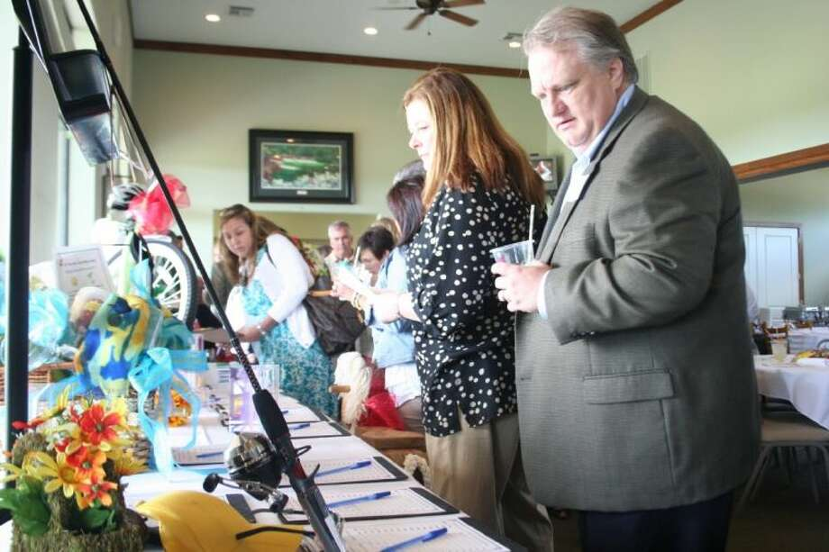 Potential buyers survey silent auction items at New Caney Independent School District Education Foundation's fundraising luncheon, Friday, May 2. Photo: Nate Brown