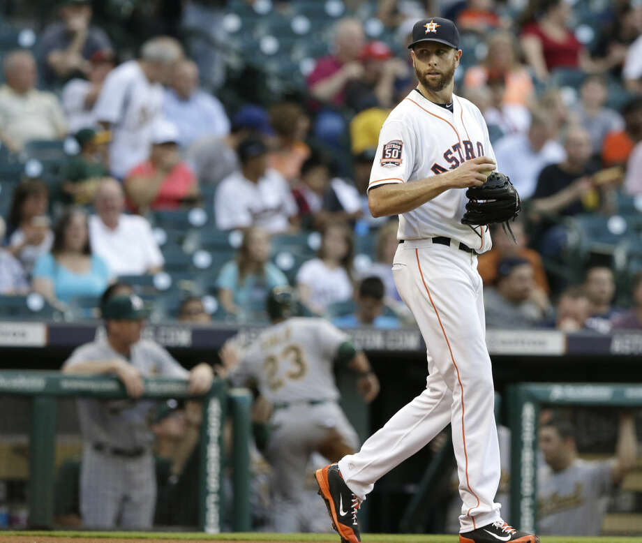 Houston Astros starting pitcher Scott Feldman walks back to the mound as Oakland Athletics' Sam Fuld (23) is welcomed back to the dugout after scoring a run on a Mark Canha double during the first inning of a baseball game Monday, April 13, 2015, in Houston. (AP Photo/Pat Sullivan) Photo: Pat Sullivan
