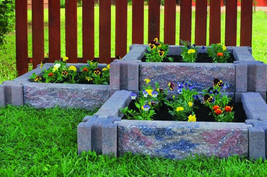 Incorporating raised flower beds using stone planters can beautify the landscape without taking a lot of time or effort. Photo credit: Courtesy of Infinity Lawn and Garden.