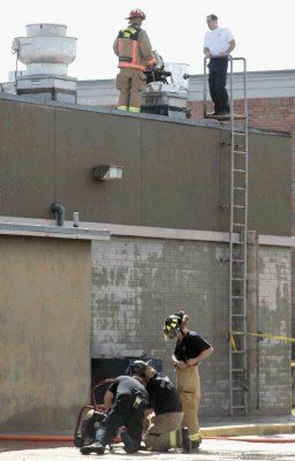 Houston Firefighters set up a fan to remove smoke as others work on the roof of the 888 Bistro Chinese restaurant after an early morning fire Monday. Photo: Kar B Hlava