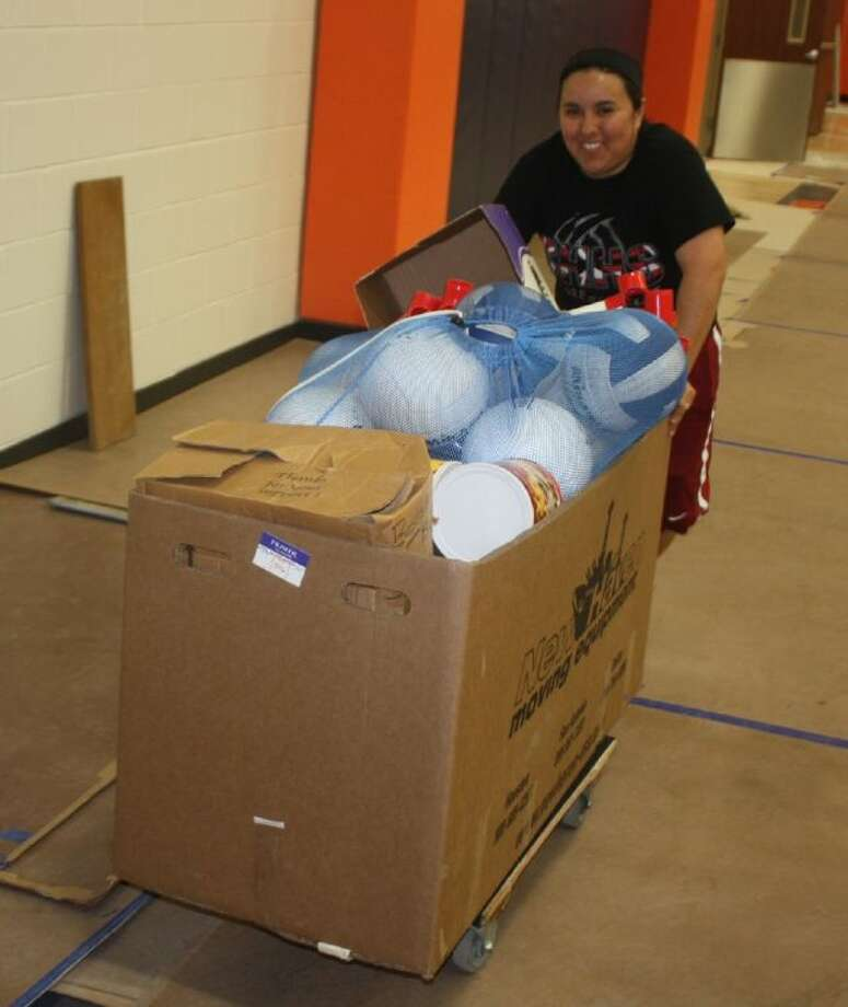 Queens Intermediate coach Cristina Lopez wheels a box of volleyballs into the brand-new school Thursday. Note the orange padding in the background. Orange, once an original color of Queens over the years, is back and very much visible in the two spacious gyms with their high ceilings.