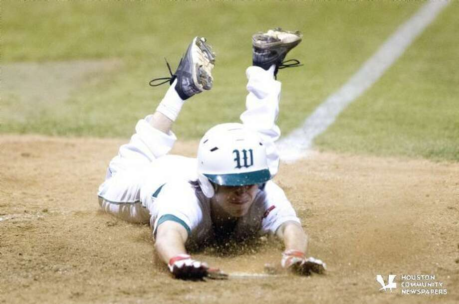 The Woodland's Casey Stokes slides into home during action from earlier this season.