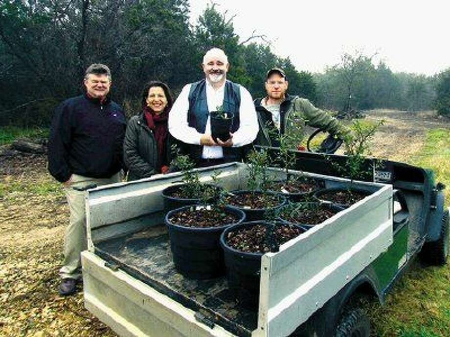 Harris County Pct. 4 Commissioner R. Jack Cagle (third from left) displays historic oak tree saplings donated by Lady Bird Johnson Wildflower Center.