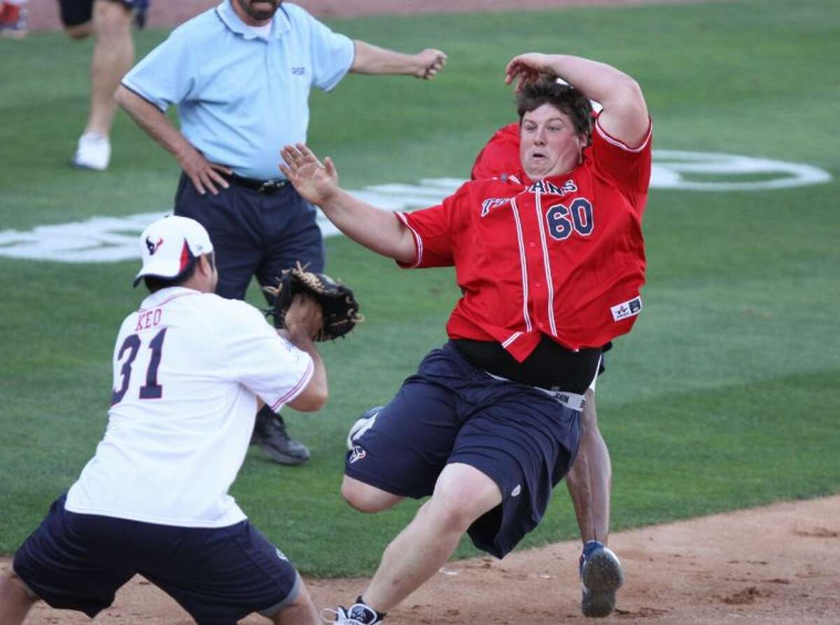 Houston Texan Ben Jones comes in sliding to home plate in the J. J. Watt Charity Classic softball game.
