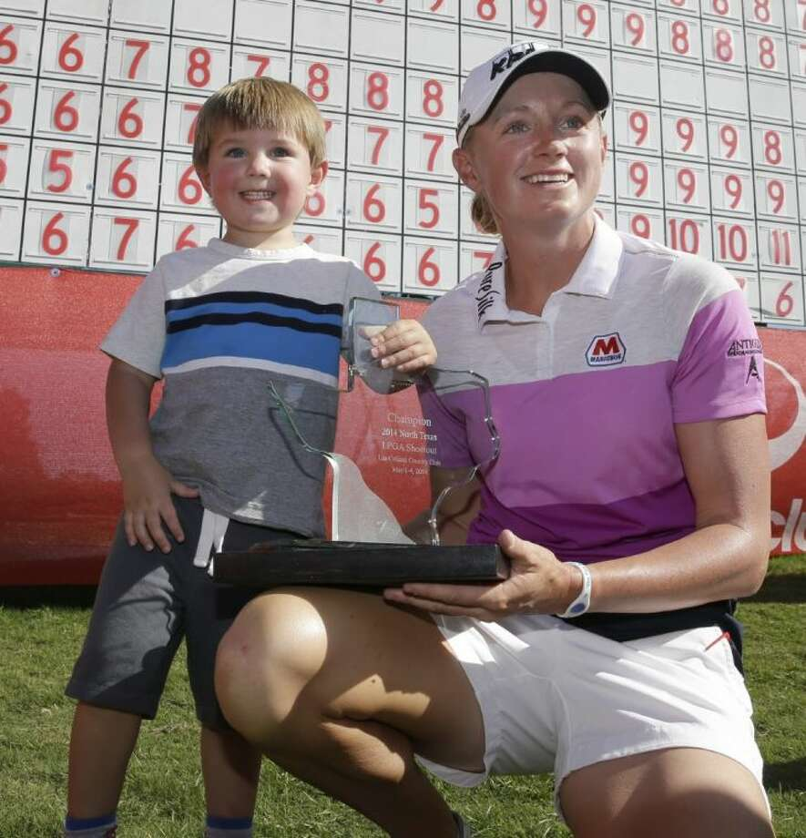 Stacy Lewis and her nephew Cole Wysocki, 3, pose for photos after she won the North Texas LPGA Shootout. Lewis fired a 64 to win by six shots.