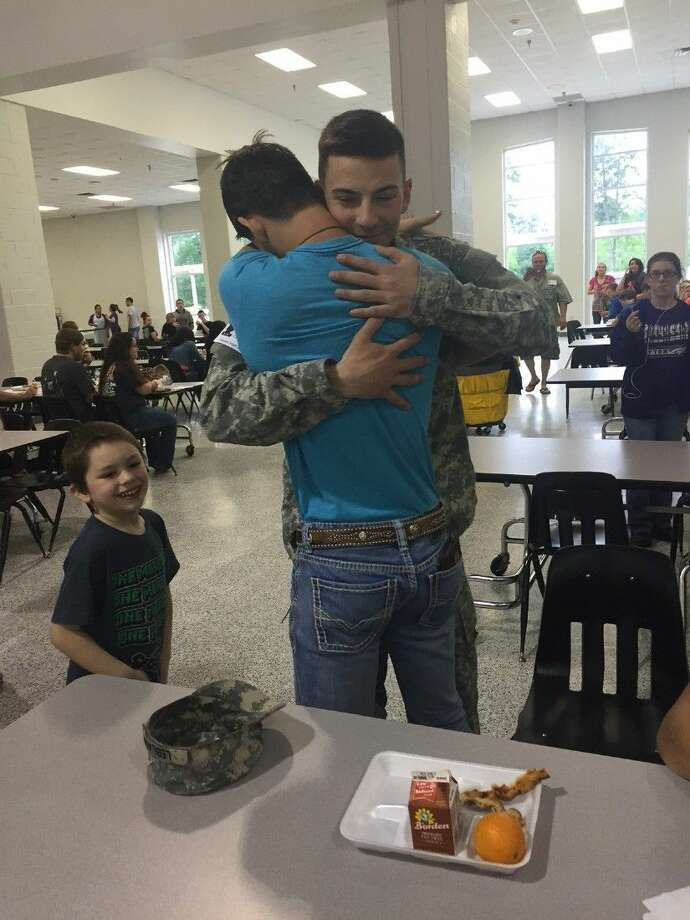 Dayton High School sophomore Alexander Messer hugs his brother, Army Private Austin LeBlanc, after the two were reunited Thursday.