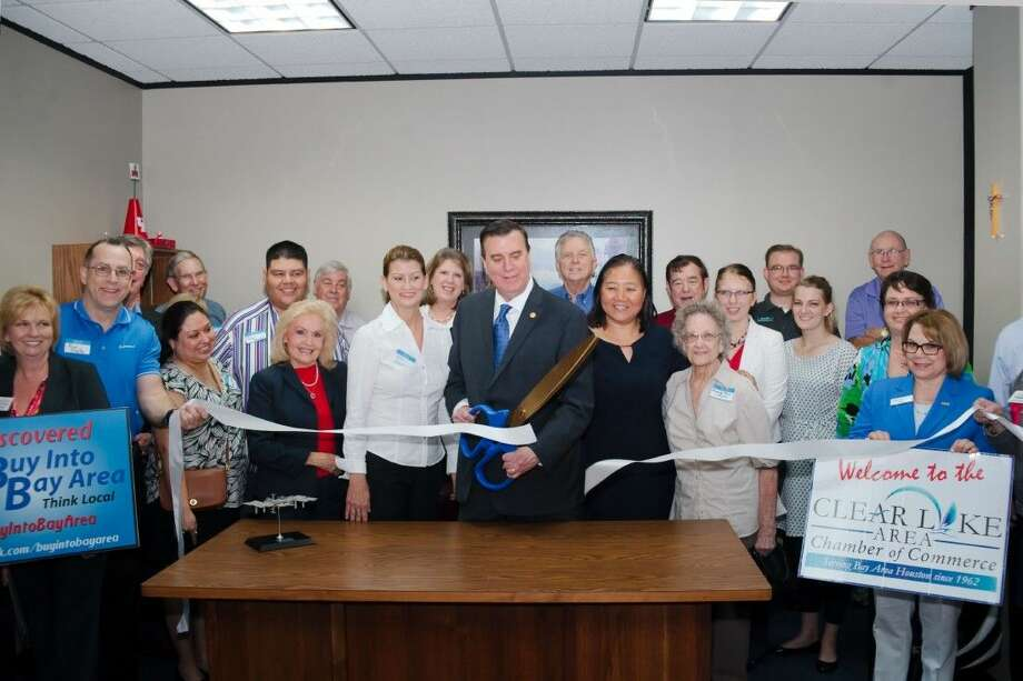 Supporters surround Texas Representative Dennis Paul, center, as he stands with his wife Eliza, center right, mother Beverly, center next right, and District Director Debra Risinger, center left, as he cuts the ribbon to celebrate the opening of his new office on El Camino Real Friday (April 10).
