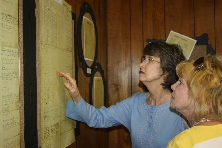 Linda Cotton and Arnette Daugherty examine historical documents on display at Thee Evergreen Congregational Church during the 150th anniversary celebration of the church. Both women do not belong to the congregation, but enjoyed the opportunity to find ancestor names on the rolls. Photo: RACHEL HALL