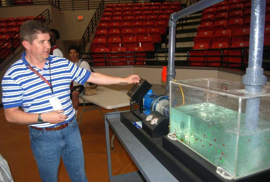 Lee College process technology instructor Bryant Dyer explains how petroleum is separated and distilled to produce new products during Tech Night, held Tuesday, April 14, 2015, at the Sports Arena on campus. The annual event allows participants to learn more about technical programs of study offered at the college.