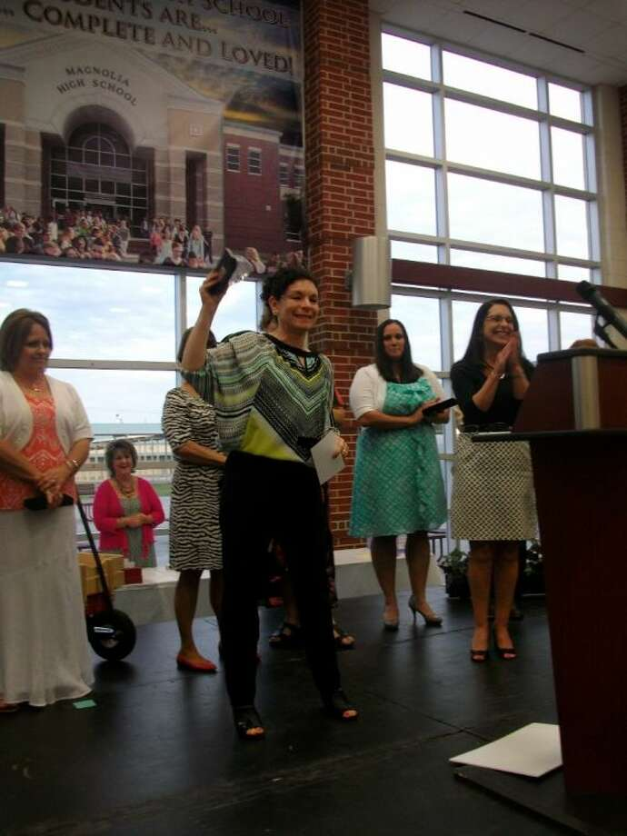 Libia Toro of Smith Elementary, holds up her award at the annual Magnolia Independent School District Teacher of Year awards banquet at Magnolia High School on Thursday, May 1, 2014. Toro won Paraprofessional of the Year.